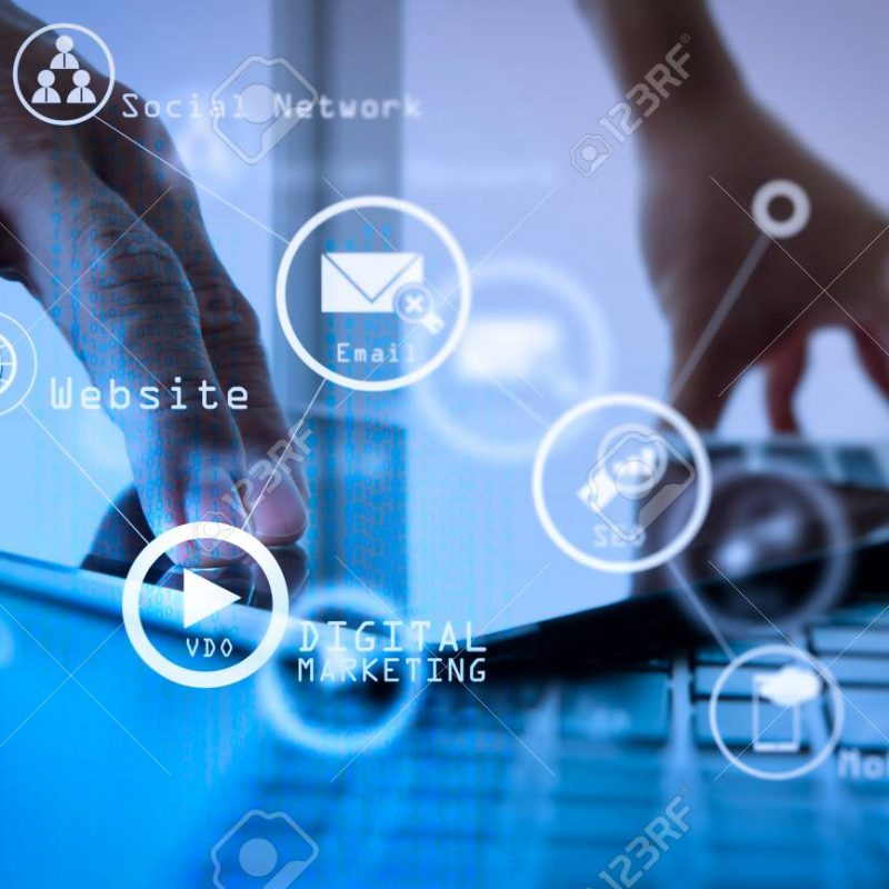 Digital marketing media (website ad, email, social network, SEO, video, mobile app) in virtual screen.businessman hand working with digital tablet and laptop on wooden desk in office.